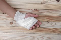 Gauze bandage the hand contusion. treating patients with hand. With a wrist left, male With gauze wrapping his injury On a wooden table . select focus front Royalty Free Stock Image