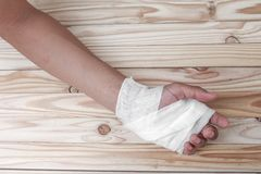 Gauze bandage the hand contusion. treating patients with hand. With a wrist left, male With gauze wrapping his injury On a wooden table . select focus front Stock Image