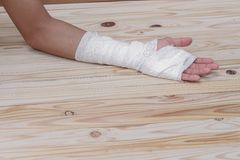 Gauze bandage the hand contusion. treating patients with hand. With a wrist left, male With gauze wrapping his injury On a wooden table . select focus front Stock Photo