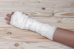 Gauze bandage the hand contusion. treating patients. With hand with a wrist left, male With gauze wrapping his injury On a wooden table . select focus front Royalty Free Stock Image