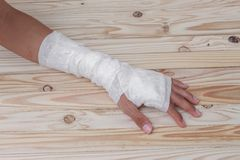 Gauze bandage the hand contusion. treating patients. With hand with a wrist left, male With gauze wrapping his injury On a wooden table . select focus front Royalty Free Stock Photo