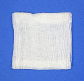 Gauze pad on blue background. A square gauze pad on a bright blue background Stock Photo