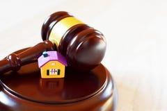 Gavel δικαστών στον υγιή φραγμό δίπλα στο κίτρινο ζωηρόχρωμο σπίτι στοκ φωτογραφία με δικαίωμα ελεύθερης χρήσης