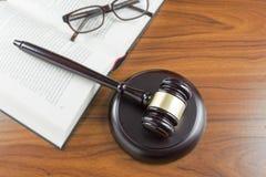 Gavel δικαστών με τον υγιή πίνακα, το ανοικτά βιβλίο και τα γυαλιά σε έναν ξύλινο στοκ φωτογραφίες