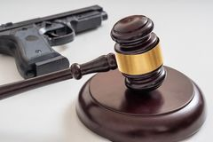 Gavel μπροστά από ένα πιστόλι Νόμοι πυροβόλων όπλων και έννοια νομοθεσίας στοκ εικόνες