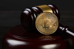 Gavel and bitcoins on a wooden desk. Dark background, Auction gavel and bitcoin symbol on black table, close-up. Bitcoin Currency Technology Business Internet royalty free stock photo