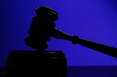 Gavel on blue. Judges court gavel silhouette on blue background Stock Photography