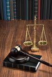 Gavel on book with golden scale. Wooden Gavel On Book With Golden Scale On Table Stock Photos
