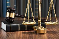 Gavel on book with golden scale Stock Images