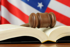Gavel on book with USA flag background. On a wood surface Royalty Free Stock Photos