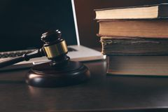Gavel with books and scales on brown background royalty free stock photo