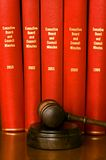 Gavel and company records. A wooden walnut gavel and sounding block in front of official red leather bound books with company records on a wooden shelf Stock Image