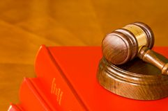 Gavel and company records. A wooden walnut gavel and sounding block sits on top of official red leather bound books with company records on a wooden shelf Stock Image