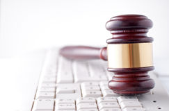 Gavel on a computer keyboard. Conceptual image of a gavel used by a judge or auctioneer with a brass band around the head lying on a computer keyboard Stock Photo