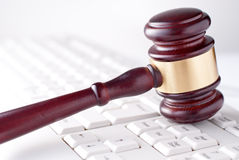 Gavel on a computer keyboard. Conceptual image of a gavel used by a judge or auctioneer with a brass band around the head lying on a computer keyboard Stock Photography