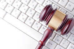 Gavel on a computer keyboard. Conceptual image of a gavel used by a judge or auctioneer with a brass band around the head lying on a computer keyboard Royalty Free Stock Images
