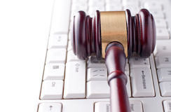 Gavel on a computer keyboard. Conceptual image of a gavel used by a judge or auctioneer with a brass band around the head lying on a computer keyboard Stock Images