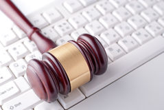 Gavel on a computer keyboard. Conceptual image of a gavel used by a judge or auctioneer with a brass band around the head lying on a computer keyboard Royalty Free Stock Image