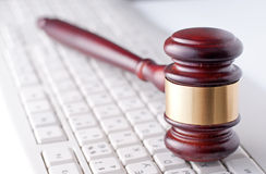 Gavel on a computer keyboard. Conceptual image of a gavel used by a judge or auctioneer with a brass band around the head lying on a computer keyboard Royalty Free Stock Photos
