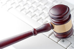 Gavel on a computer keyboard. Conceptual image of a gavel used by a judge or auctioneer with a brass band around the head lying on a computer keyboard Stock Photos