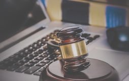 Gavel on computer with legal books Royalty Free Stock Images