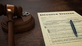 Gavel Divorce Paper Decree Front. Front low shot of a divorce decree paper with a pen, gavel and rings in the scene Royalty Free Stock Photos