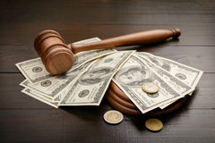 Gavel with dollars and cents. On a brown lacquered wooden table close up. Concept of corruption and bribery stock photo