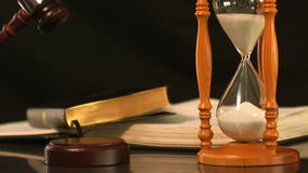 Gavel dropping on sounding block beside hourglass and bible