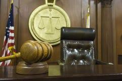 Gavel et la chaise du juge dans la salle d'audience Images stock
