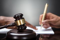 Gavel In Front Of Person`s Hand Signing Legal Document stock photos