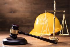 Gavel In Front Of Yellow Safety Helmet And Golden Scale. Judge Gavel In Front Of Yellow Safety Helmet And Golden Scale On The Wooden Table Royalty Free Stock Images