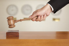 Gavel in hand. Judge holding gavel against the clock Royalty Free Stock Images