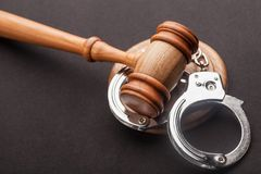 Gavel and handcuffs. Courtroom arbitrate attention auction bid black Stock Image