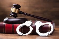 Gavel And Handcuffs On Law Book. Gavel And Handcuffs On The Law Book Over The Wooden Table Background stock photography