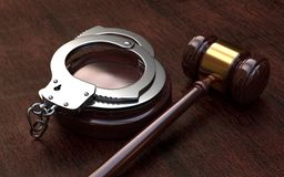 Gavel and handcuffs on wooden table background stock image