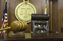 Gavel And Judge's Chair In Courtroom. Closeup of gavel and wooden block on table with judge's chair in courtroom stock images