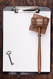 Gavel and Key. On a clipboard with white paper. Add your text to the paper Stock Photography