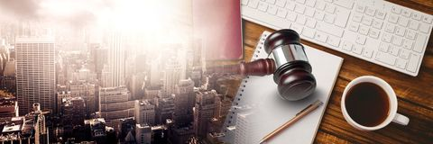 Gavel and keyboard with notepads and coffee on desk with transition. Digital composite of Gavel and keyboard with notepads and coffee on desk with transition Royalty Free Stock Photography