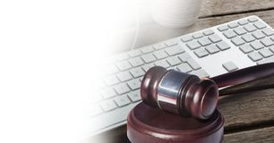Gavel and keyboard with white transition. Digital composite of Gavel and keyboard with white transition Royalty Free Stock Photo