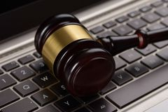 Gavel on laptop. Close Up Of Wooden Brown Gavel On Laptop stock photo