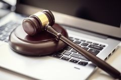 Justice gavel on laptop computer keyboard. Gavel on laptop computer keyboard concept for online internet auction or legal attorney assistance Royalty Free Stock Images
