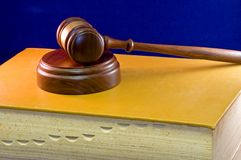Gavel on law book. A view of a wooden gavel and sounding block resting on a large indexed law book on a blue velvet background Stock Image