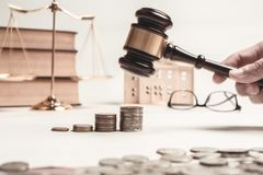 Gavel of lawyer with education book, house model and coin.