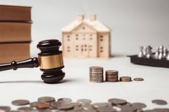 Gavel of lawyer with education book, house model and coin. Stock Photos