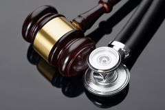Gavel and medical stethoscope. Close-up Of Brown Gavel And Medical Stethoscope Stock Images