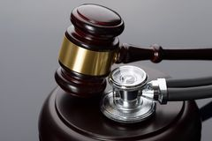 Gavel and medical stethoscope. Close-up Of Brown Gavel And Medical Stethoscope Royalty Free Stock Images