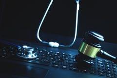 Gavel with medical stethoscope on laptop keyboard royalty free stock image
