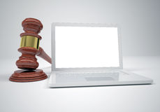 Gavel and open white laptop. The gray background Royalty Free Stock Photo