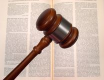 Gavel over law book. Gavel in front of an open law book. The text of the book is out of focus royalty free stock images