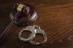 Gavel and Pair of Handcuffs on Table. Gavel and Pair of Handcuffs on Wooden Table Stock Photos